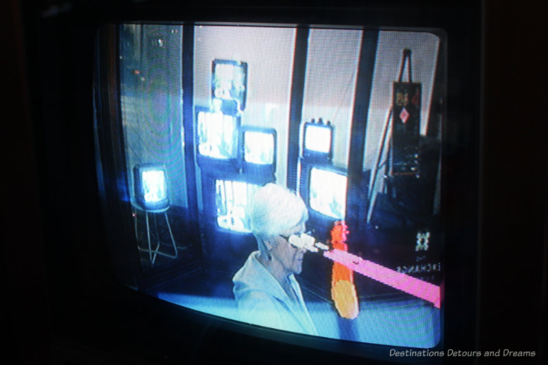 Light beams emanating from a woman's eyes on a CRT screen as part of art installation Luv Lite