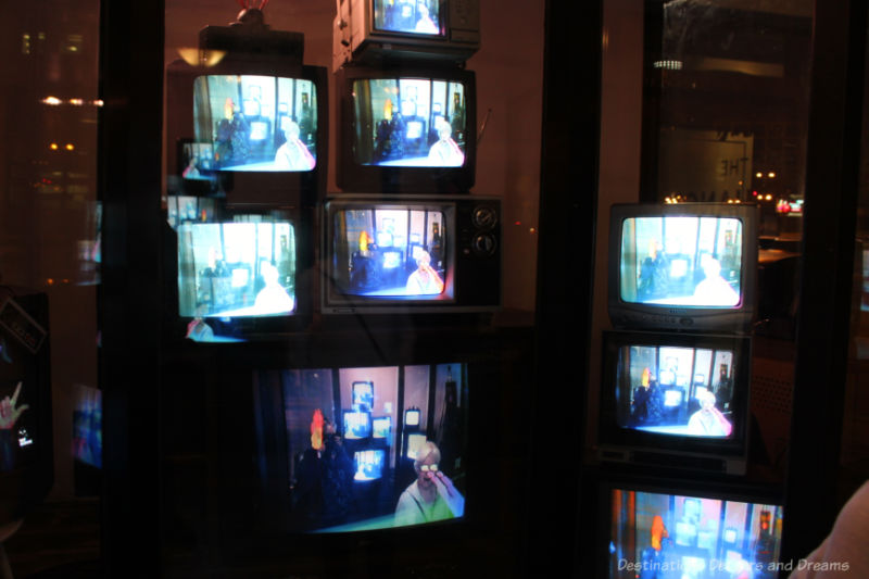 A collection of CRT screens in a display window showing an augmented reality version of an audience member